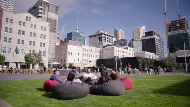 vidéos et rushes de friends sitting on beanbags in public square - nouvelle zélande