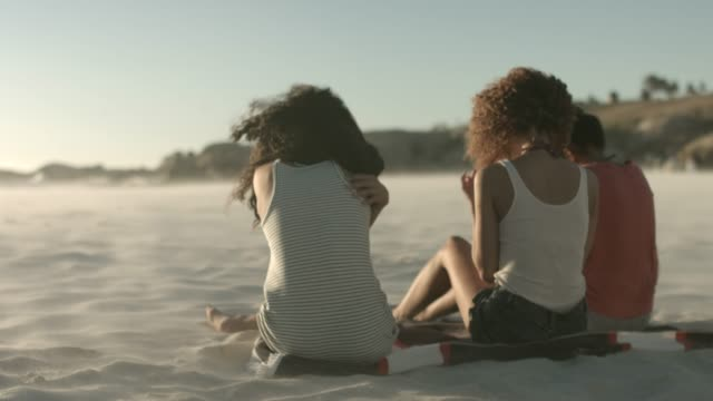 Friends sitting on mat at windy beach