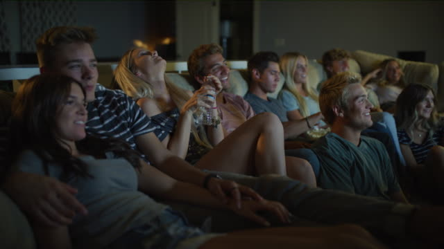 friends sitting on sofa watching comedy movie on television / cedar hills, utah, united states - teenagers only bildbanksvideor och videomaterial från bakom kulisserna