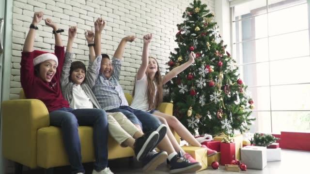 freunde, die auf dem sofa sitzen und an weihnachten jubeln - ziegel stock-videos und b-roll-filmmaterial