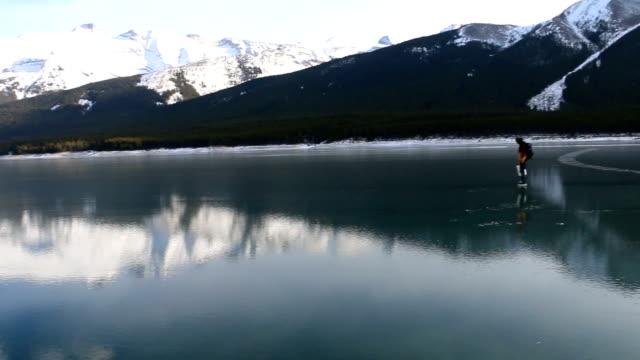 vídeos de stock, filmes e b-roll de patim de amigos ao longo do lago alpino congelado para peixes de gelo - esporte de inverno