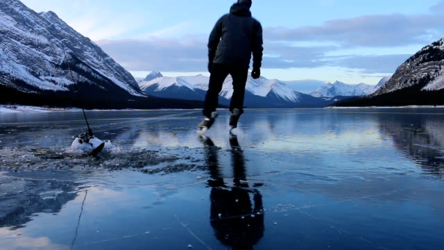 friends skate along frozen alpine lake to ice fish - ice skating stock videos & royalty-free footage