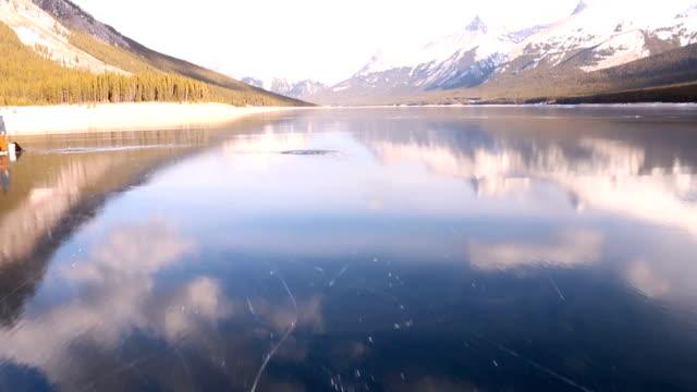 friends skate along frozen alpine lake to ice fish - frozen stock videos & royalty-free footage