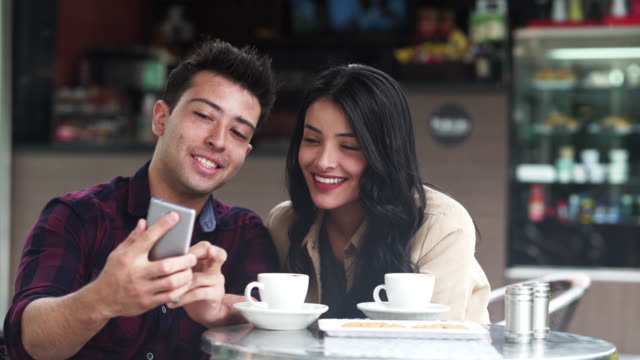 friends smiling while looking at the cell phone - colombian ethnicity stock videos & royalty-free footage