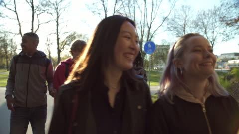 vídeos y material grabado en eventos de stock de friends smiling while walking below bridge - 18 19 años