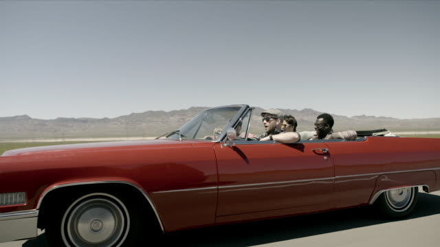Friends speed down desert highway in classic red convertible