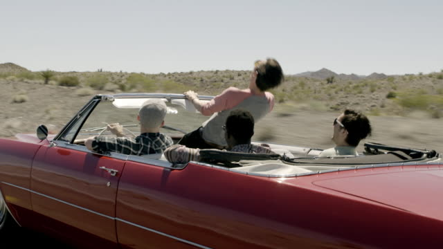 Friends speed through desert in classic convertible, guy stands up and howls into the wind