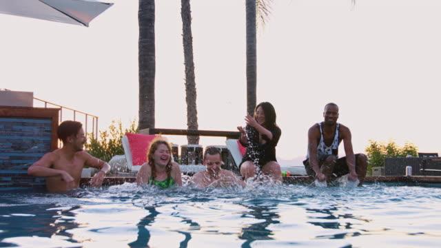 Freunde, die einander im Schwimmbad plantschen