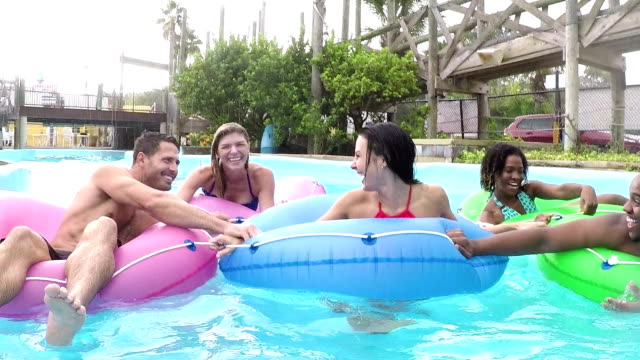 friends splashing on lazy river at water park - water park stock videos and b-roll footage