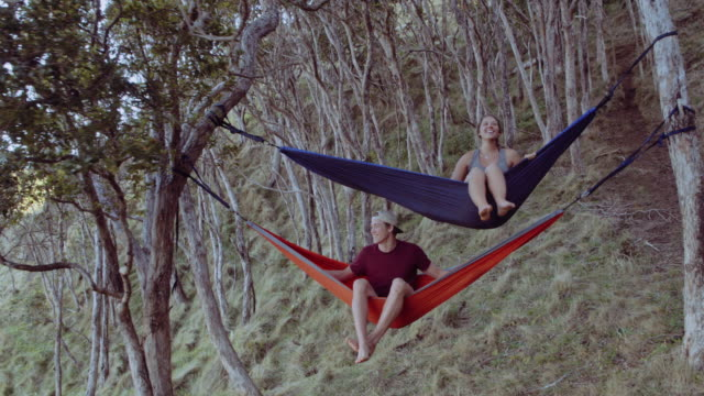 Friends suspended in hammocks next to hiking trail