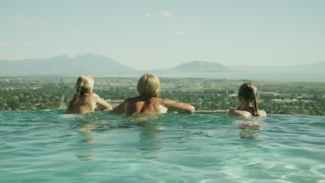 vídeos de stock, filmes e b-roll de ws friends (14-19) swimming in infinity pool / cedar hills, utah, usa - lago infinito
