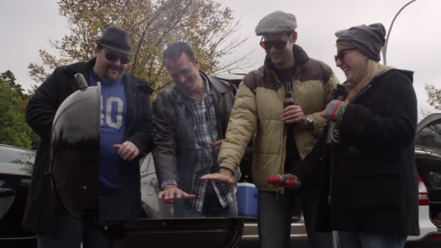 friends tailgating in a cold parking lot - beer cap stock videos & royalty-free footage
