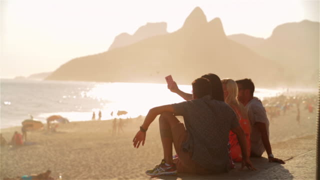 Friends take selfie sitting on boardwalk overlooking Ipanema Beach