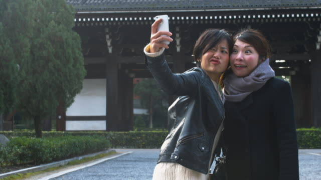 Friends taking a selfie at a Japanese temple