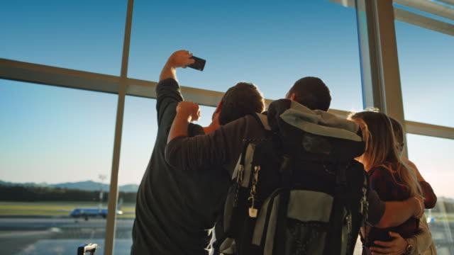 friends taking a selfie by the glass wall of the sunny airport building - reportage stock videos & royalty-free footage
