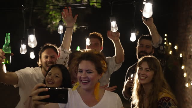 裏庭でパーティーをしながら自分撮りをする友人 - 宅地点の映像素材/bロール