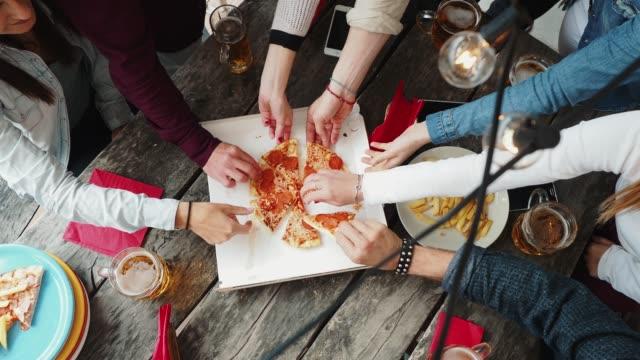 vidéos et rushes de amis prenant une tranche de pizza de la boîte à pizza - déjeuner