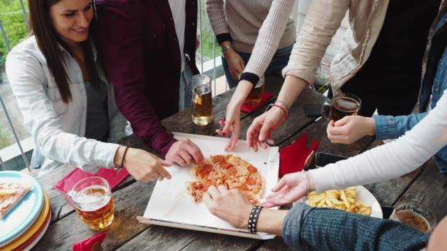 friends taking a slice of pizza from the pizza box - group of objects stock videos & royalty-free footage