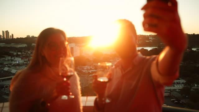 vídeos y material grabado en eventos de stock de amigos tomando selfie y bebiendo vino al atardecer - vino tinto