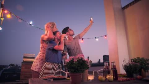 friends taking selfies on urban rooftop - europäischer abstammung stock-videos und b-roll-filmmaterial