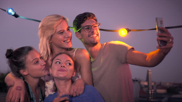 friends taking selfies on urban rooftop - terrazza video stock e b–roll