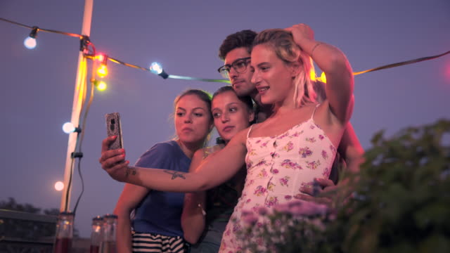 Friends taking selfies on urban rooftop