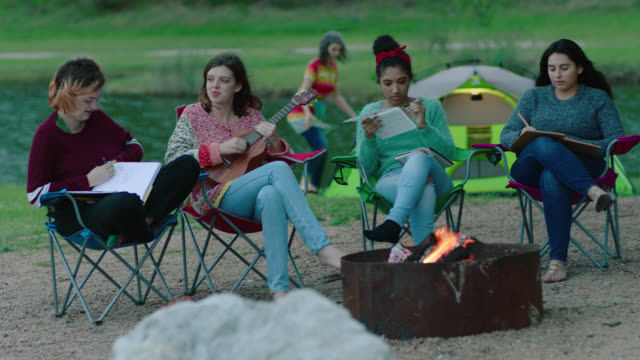 WS. Friends talk and draw and play ukulele by fire pit while mom sets up campsite.