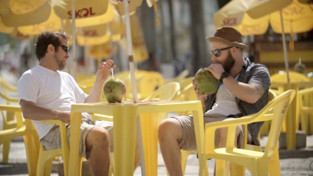 friends talk and drink from coconuts at sunny outdoor caf_ in rio - pavement cafe stock videos & royalty-free footage
