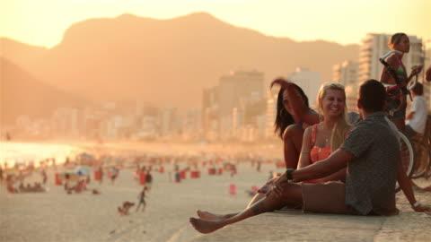 friends talk and high-five in the sun overlooking ipanema beach - rio de janeiro bildbanksvideor och videomaterial från bakom kulisserna