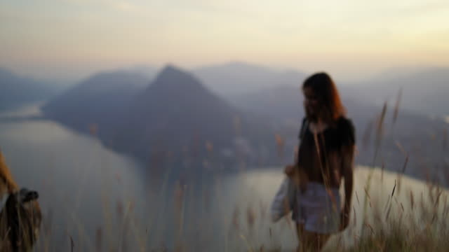 friends talking and laughing on mountain top overlooking lake and city below - dissolvenza in chiusura video stock e b–roll