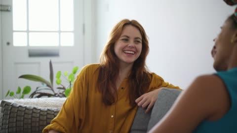 vídeos y material grabado en eventos de stock de friends talking and smiling on sofa - two people