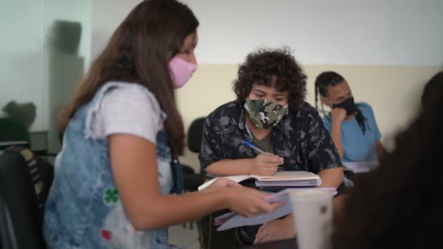 vidéos et rushes de amis parlant pendant la classe - portant le masque facial - commencement