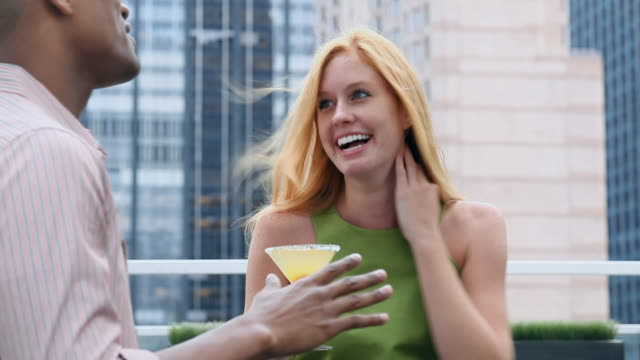 Friends talking on rooftop bar and drinking cocktails