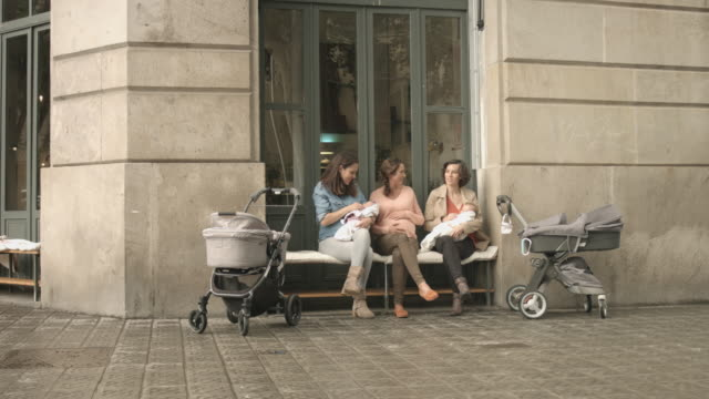 friends talking while carrying babies on outdoors - three wheeled pushchair stock videos & royalty-free footage