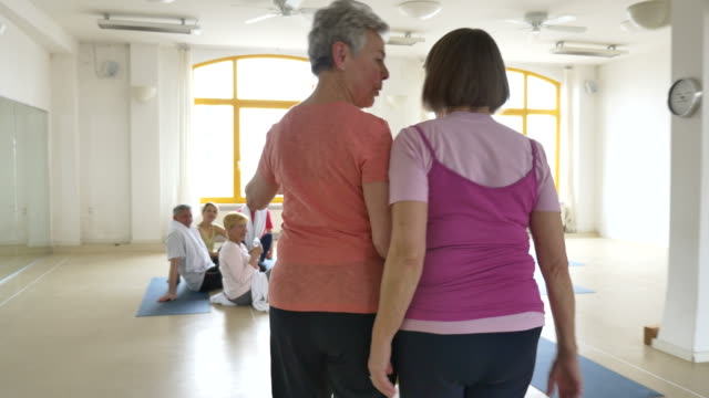 Friends talking while greeting in yoga class stock footage video friends talking while greeting in yoga class stock footage video getty images m4hsunfo