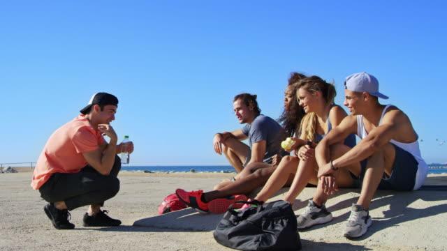 vídeos de stock, filmes e b-roll de amigos conversando enquanto descansava na praia contra o céu - male friendship