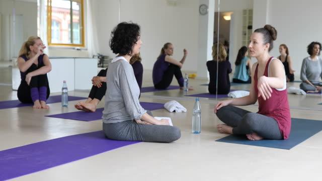 vídeos y material grabado en eventos de stock de amigos hablando mientras descansa en la clase de yoga - centro de yoga