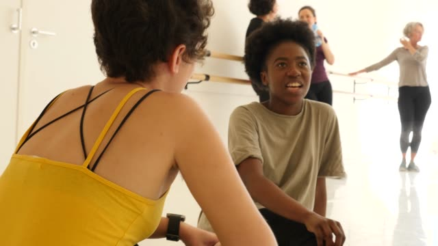 Vrienden praten zittend in dans klasse