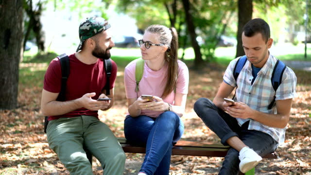 vídeos de stock e filmes b-roll de friends texting on their phones - banco assento