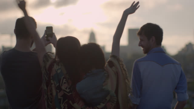 vidéos et rushes de friends throw hands in the air and take smartphone photos overlooking austin, texas skyline - arrivée