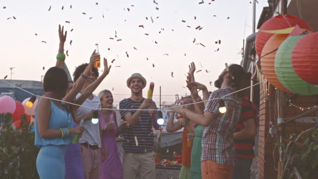friends throwing confetti at rooftop party - party social event stock videos and b-roll footage