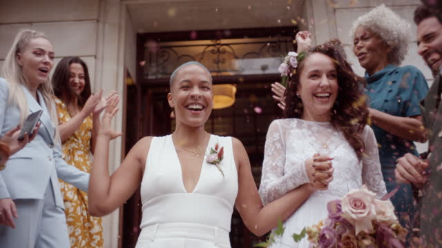 friends throwing confetti on newlywed lesbian couple - married stock videos & royalty-free footage