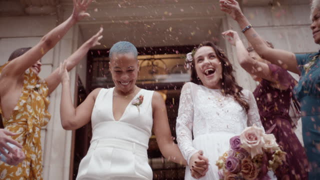 friends throwing confetti on newlywed lesbian couple - non us film location stock videos & royalty-free footage