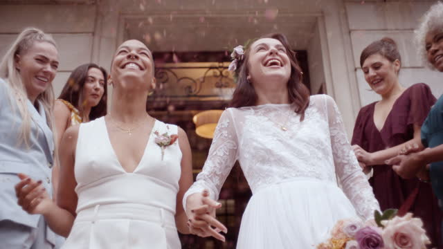 friends throwing confetti on newlywed lesbian couple - wedding stock videos & royalty-free footage