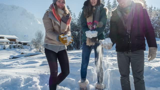 friends throwing snow - wintermantel stock-videos und b-roll-filmmaterial