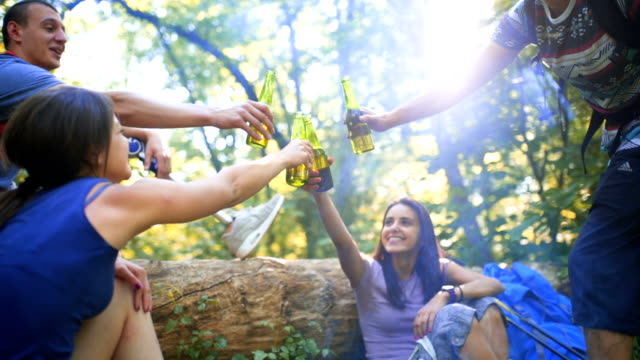 Friends toast with beer near campfire