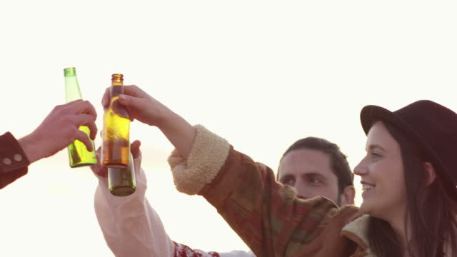 friends toasting beer bottles on terrace in summer - celebratory toast stock videos & royalty-free footage