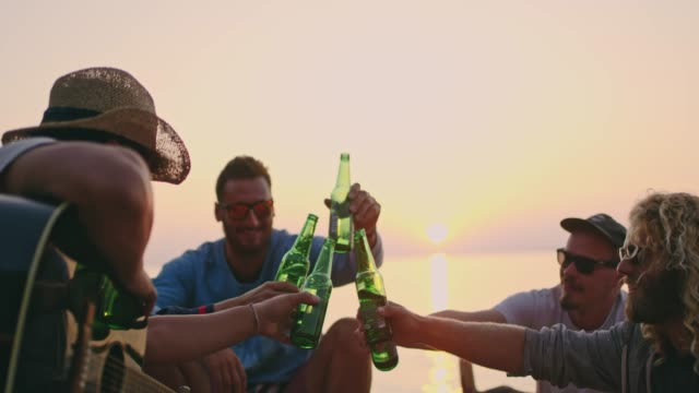 vídeos de stock e filmes b-roll de friends toasting beer bottles on tranquil sunset beach, slow motion - beber