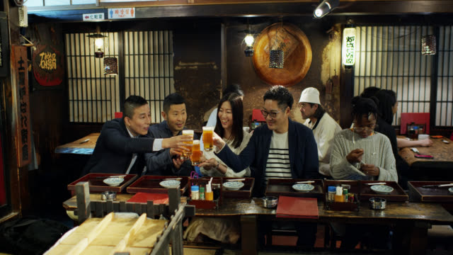 amici che brindano birre nell'affollato ristorante di tokyo - happy hour video stock e b–roll