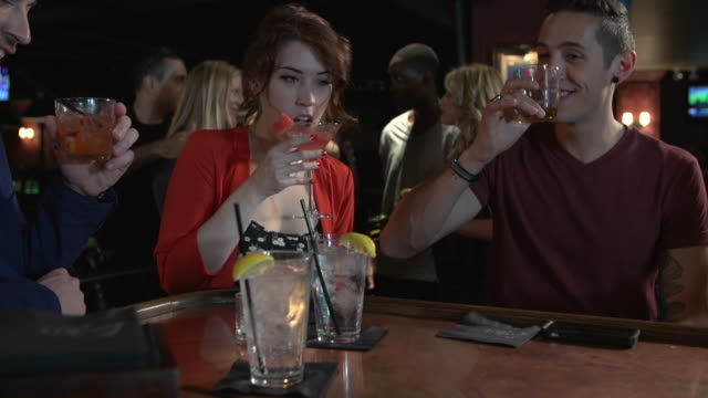 friends toasting cocktails at a bar - happy hour stock-videos und b-roll-filmmaterial